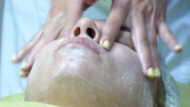 Beautician hands stroking the face of the client with cream. Facial massage beautiful girl. Portrait of a young woman in the beauty salon. Cosmetologist doing massage of female face. Close-up. video