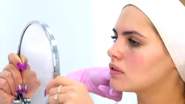 kosmetikerin berät frau klientin, die spiegelbildlichen blick in die schönheitsklinik hat. - kosmetik beratung stock-videos und b-roll-filmmaterial
