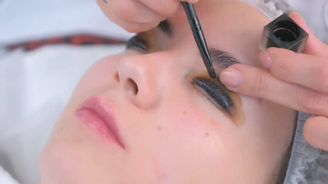 Beautician is painting client's woman eyelashes in black, face closeup. video