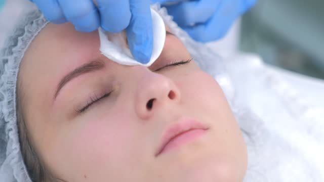 Beautician is wiping eyebrows using cotton pads making eyebrows microblading. video