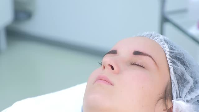 Beautician making eyebrows microblading procedure in beauty salon for woman. video