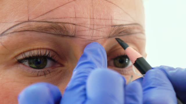 Beautician marking new eyebrow shape for microblading on female face closeup