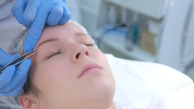 Beautician plucks out hair on eyebrows with tweezers for woman, face closeup. video