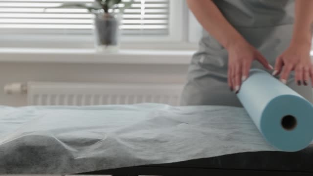 Beautician rolls fabric onto a couch