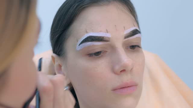 Beautician tinting woman eyebrows applying brown paint use brush, face closeup. video