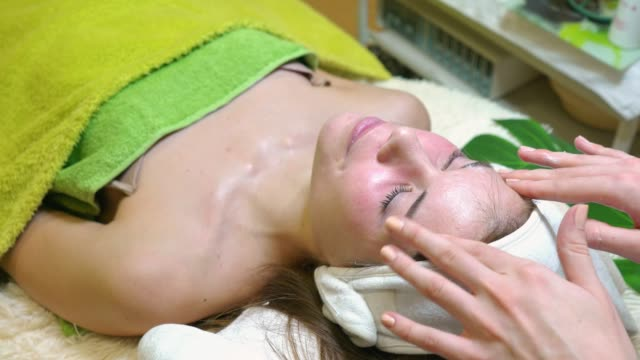 顔の治療後、顔を優しくマッサージする顔のクリームを使用しての美容師 ビデオ