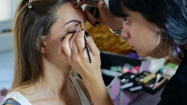försköning i skönhetssalongen ägs av latina tusenåriga kvinna - makeup artist bildbanksvideor och videomaterial från bakom kulisserna
