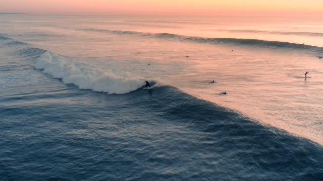 vídeos de stock e filmes b-roll de beautiful aerial view of a profesional surfer surfing a perfect wave on a sunset / sunrise. - portugal