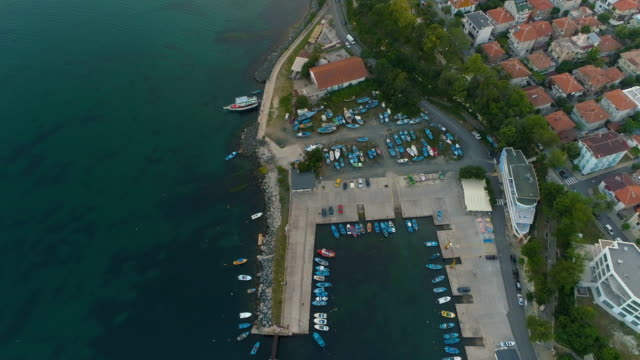 vídeos de stock e filmes b-roll de beautiful aerial view of anchored fisherman boats on the quay with lighthouse - fishman