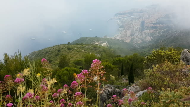 Beautiful Aerial View of Monaco From the Mountain Aerial View of Mountain with Fog and Flowers. Principality of Monaco in the Background - 4K Video monte carlo stock videos & royalty-free footage