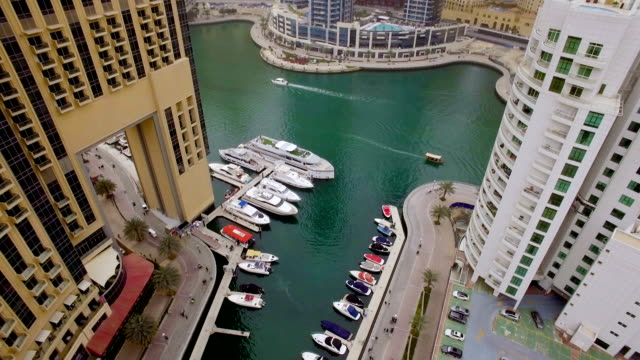 beautiful aerial view of the promenade among the skyscrapers, the water and yachts. The promenade walk people video