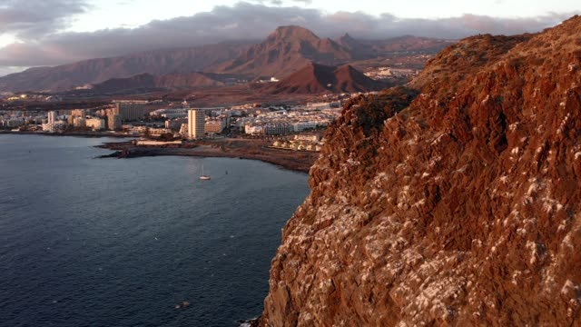 beautiful aerial view of the south coast of tenerife and the town of los cristianos at sunset - południe kierunek filmów i materiałów b-roll
