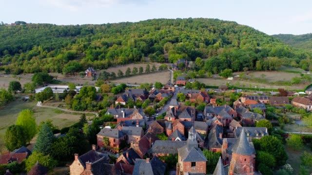 vídeos de stock, filmes e b-roll de vista aérea bonita sobre a vila de collonges-la-rouge em france. a aldeia está no meio de uma floresta e campos verdes. - aldeia