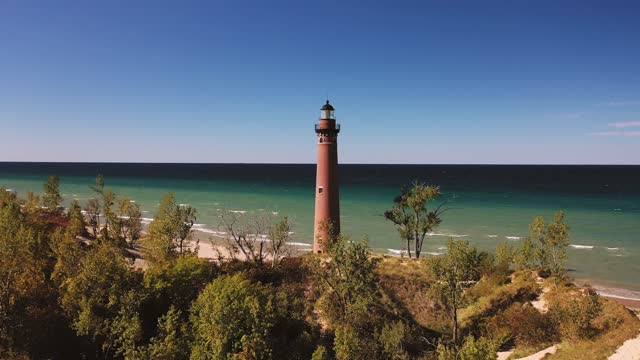 Beautiful aerial view panning in and up towards the Little Sable Lighthouse along the shoreline of Lake Michigan sitting amongst vegetation and tree covered sand dunes with a clear blue sky above.