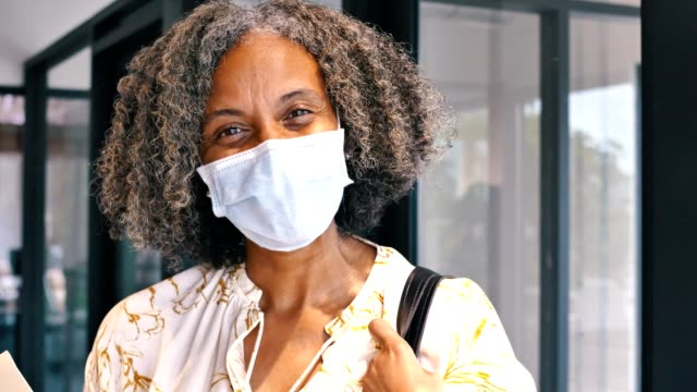 Beautiful African American businesswoman in her office A beautiful mature African American businesswoman stands in her office wearing a protective face mask. She is working in an office during the coronavirus pandemic. She looking at the camera and is holding a file folder. black people stock videos & royalty-free footage