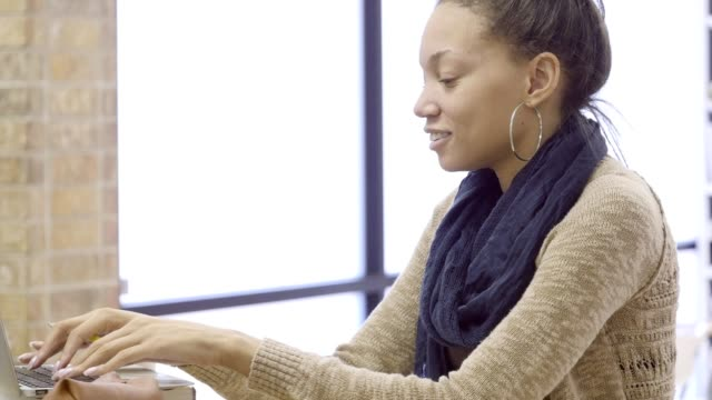 Beautiful African American college student works on research assignment in library video