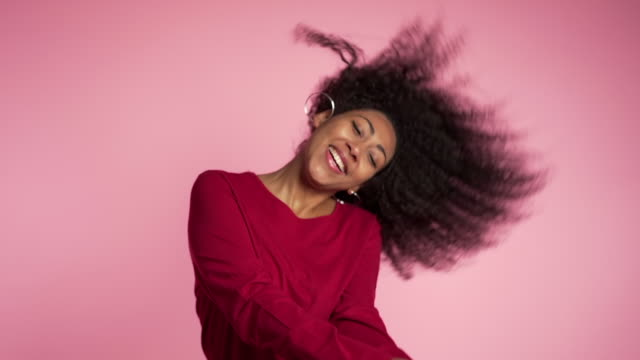 Beautiful african american woman with afro hair having fun smiling and dancing in studio against pink background. slow motion