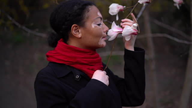 Beautiful african girl with vitiligo standing on the street sniffs spring flowers. Magnolia  spring blossom. Portrait of a girl with skin problems. Autumn season. Woman lifestyle