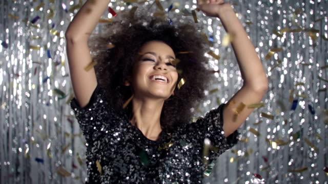 stockvideo's en b-roll-footage met mooie afro amerikaanse vrouw dansen onder gouden confetti, slow motion. - afro amerikaanse etniciteit