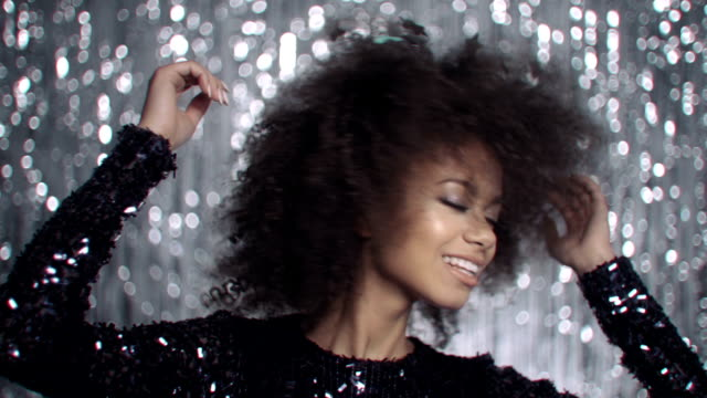 Beautiful afro american woman dancing among golden confetti, slow motion. video