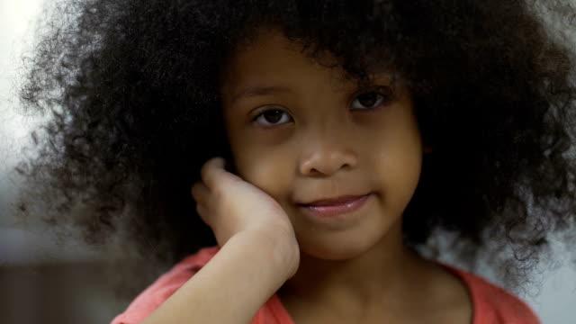 vídeos de stock, filmes e b-roll de linda criança afro-americana, sorrindo para a câmera, emoções positivas, closeup - menina negra
