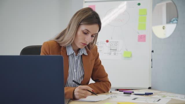 vidéos et rushes de belle femme d'affaires américaine écrivant dans le document, travaillant au bureau avec l'ordinateur portatif dans le bureau - bloc note