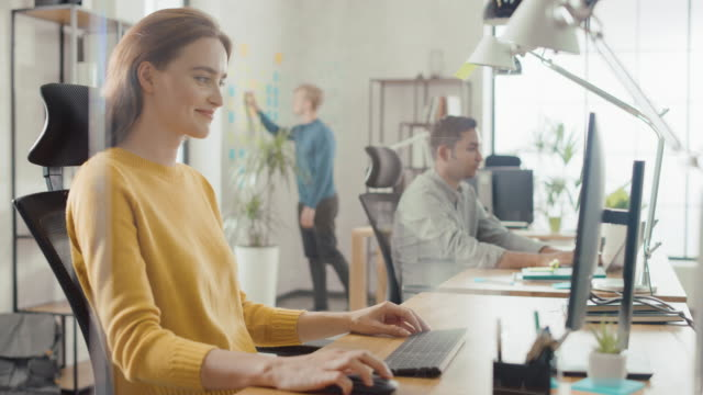 Beautiful and Creative Young Woman Sitting at Her Desk Using Laptop Computer. In the Background Bright Office where Diverse Team of Young Professionals Work
