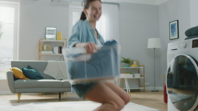 美しく、幸せなブルネット若い女性ダンス、家庭的なジーンズ服洗濯機に向かって移動します。彼女は汚れた洗濯物と洗濯機を読み込みます。明るく広々 としたリビング ルームとモダンな� - 楽しい 洗濯点の映像素材/bロール