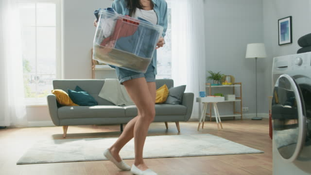 beautiful and happy brunette young woman dancing and moving towards the washing machine in homely jeans clothes. she loads the washer with dirty laundry. bright and spacious living room with modern interior. - pranie filmów i materiałów b-roll