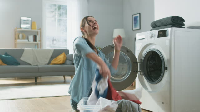 beautiful and happy brunette young woman is sitting next to the washing machine in homely jeans clothes. she laughts and throws laundry clothes into the air. bright and spacious living room with modern interior. - pranie filmów i materiałów b-roll