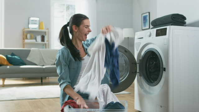 美しく、幸せなブルネット若い女が座って次家庭的なジーンズ服で洗濯機へ。彼女の大笑いと空気中にスロー洗濯物。明るく広々 としたリビング ルームとモダンなインテリア。 - 楽しい 洗濯点の映像素材/bロール