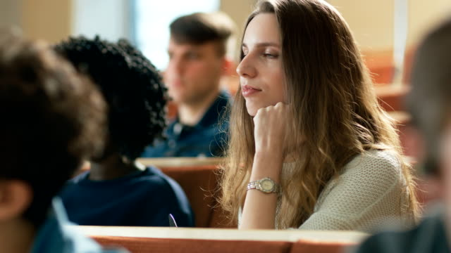 Beautiful and Intelligent Young Girl Listens to a Lecture in a Classroom Full of Multi Ethnic Students. Shallow Depth of Field. video