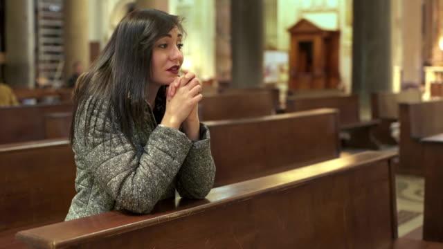 beautiful and sad woman praying in church - jesus christ filmów i materiałów b-roll