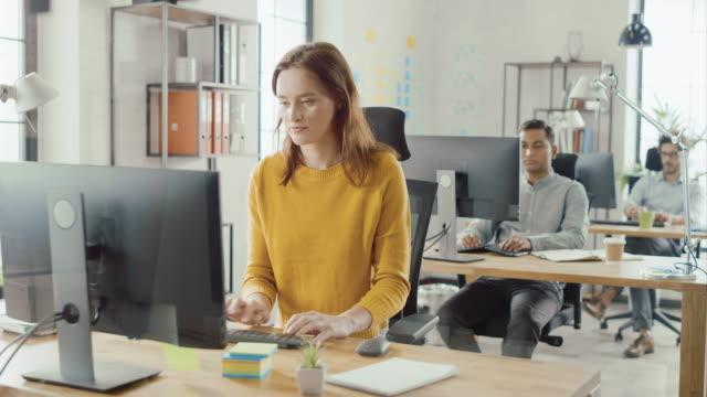 vidéos et rushes de belle et intelligente spécialiste féminine aux cheveux rouges assise à son bureau fonctionne sur un ordinateur de bureau. dans le contexte modern bright office avec divers groupes de professionnels travaillant pour la croissance startup - marketing
