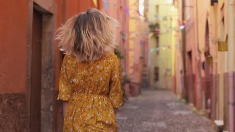 vidéos et rushes de une jeune fille belle et souriante se promène dans les rues de la ville italienne. - italie