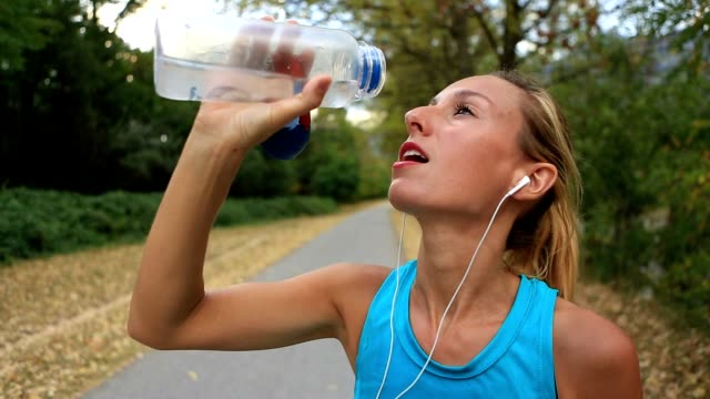 Beautiful and sporty young woman drinking water after jogging outdoors video