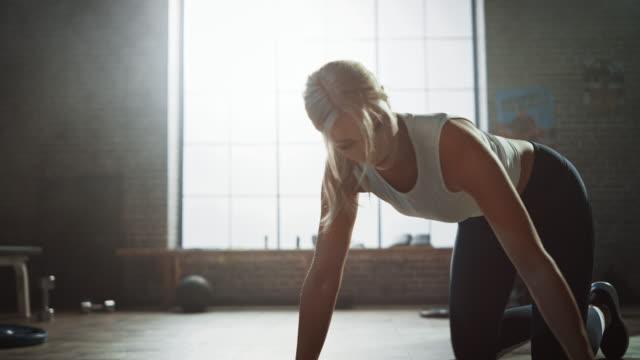 Schöne und junge Mädchen verwendet Smartphone App Timer für ihre Übung einzurichten und beginnt, Running Plank auf ihrer Fitness-Matte zu tun. Athletische Frau tut Bergsteiger Training in stilvollen Hardcore Gym – Video