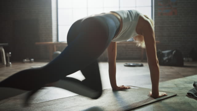 Beautiful and Young Girl Uses Smartphone App to Setup Timer For Her Exercise and Starts doing Running Plank on Her Fitness Mat. Athletic Woman Does Mountain Climber Workout in Stylish Hardcore Gym