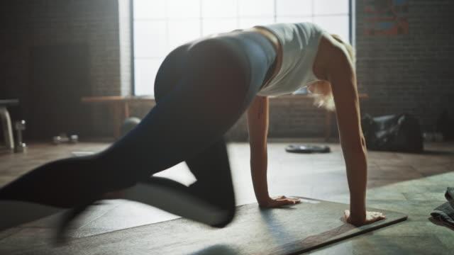 bella e giovane ragazza utilizza l'app per smartphone per configurare il timer per il suo esercizio fisico e inizia a fare plank da corsa sul suo tappetino fitness. la donna atletica fa allenamento di alpinismo nell'elegante palestra hardcore - esercizio fisico video stock e b–roll