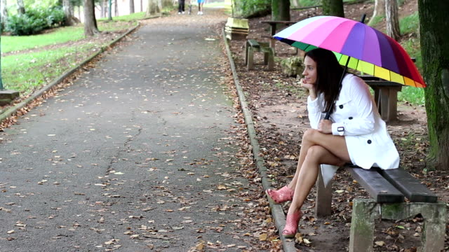 Beautiful angry girl sitting alone and waiting Beautiful angry girl sitting alone and waiting under a rainbow umrella cross legged stock videos & royalty-free footage