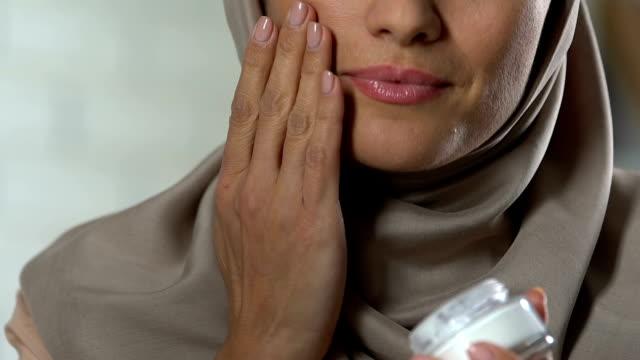 Beautiful arab female applying anti-age cream on face, enjoying her appearance Beautiful arab female applying anti-age cream on face, enjoying her appearance serum sample stock videos & royalty-free footage