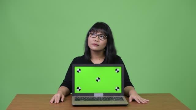 vídeos y material grabado en eventos de stock de hermosa empresaria asiática pensando mientras mostraba portátil - sudeste