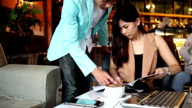 Hermosa pareja asiática de negocios con estilo sentados en la acogedora cafetería y haciendo lista de planificación para fin de semana - vídeo