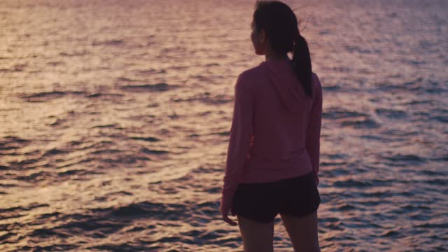 A beautiful asian female runner looks at the sea view while standing on the beach.