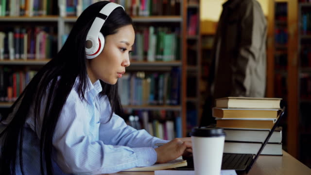 beautiful asian female student in headphones sitting at desk in library working concentrated at school project. young girl typing on laptop, drinking coffee and writing in copybook - struttura pubblica video stock e b–roll