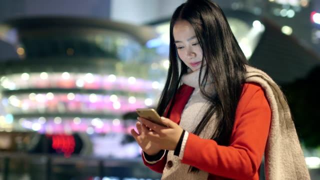 beautiful asian girl using smart phone in modern city at night video