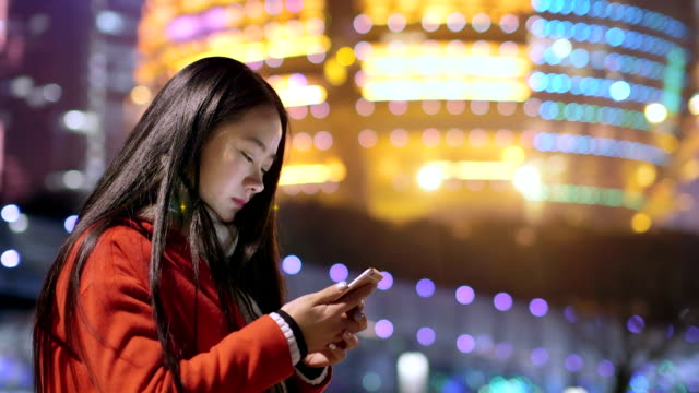 beautiful asian girl using smart phone in modern city at night video