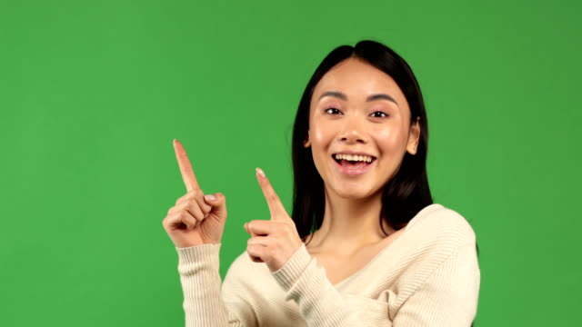 vídeos de stock e filmes b-roll de beautiful asian girl with natural make-up with black hair and a light sweater points her fingers to the side on an isolated background - europe points