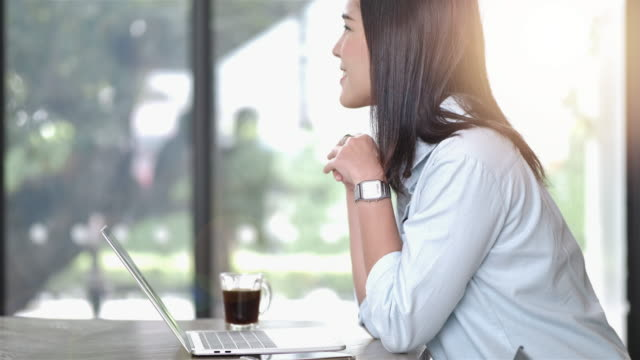 Beautiful Asian girl working and relax at coffee shop connected on laptop computer.  new generation and Lifestyle working concept. Slow Motion video