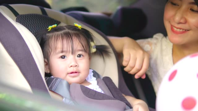 Beautiful asian Mother putting baby in car seat video